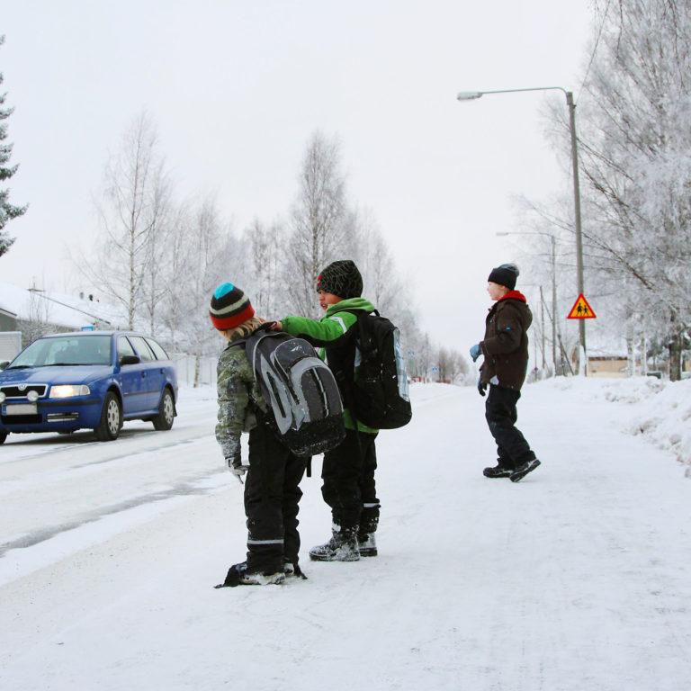 Kuvassa lapsia kävelytiellä katsomassa auton menoa ohi.