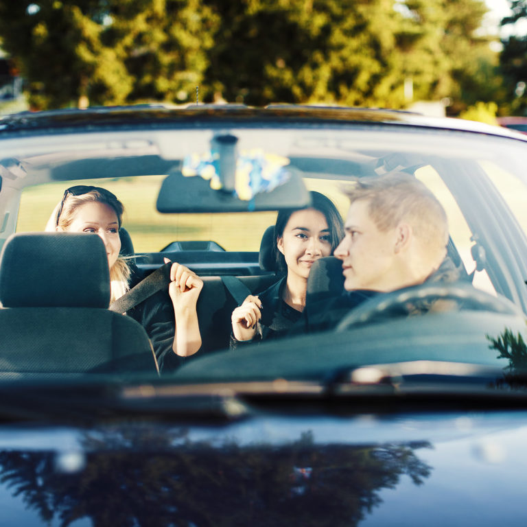 Kuvassa nuoria autossa.