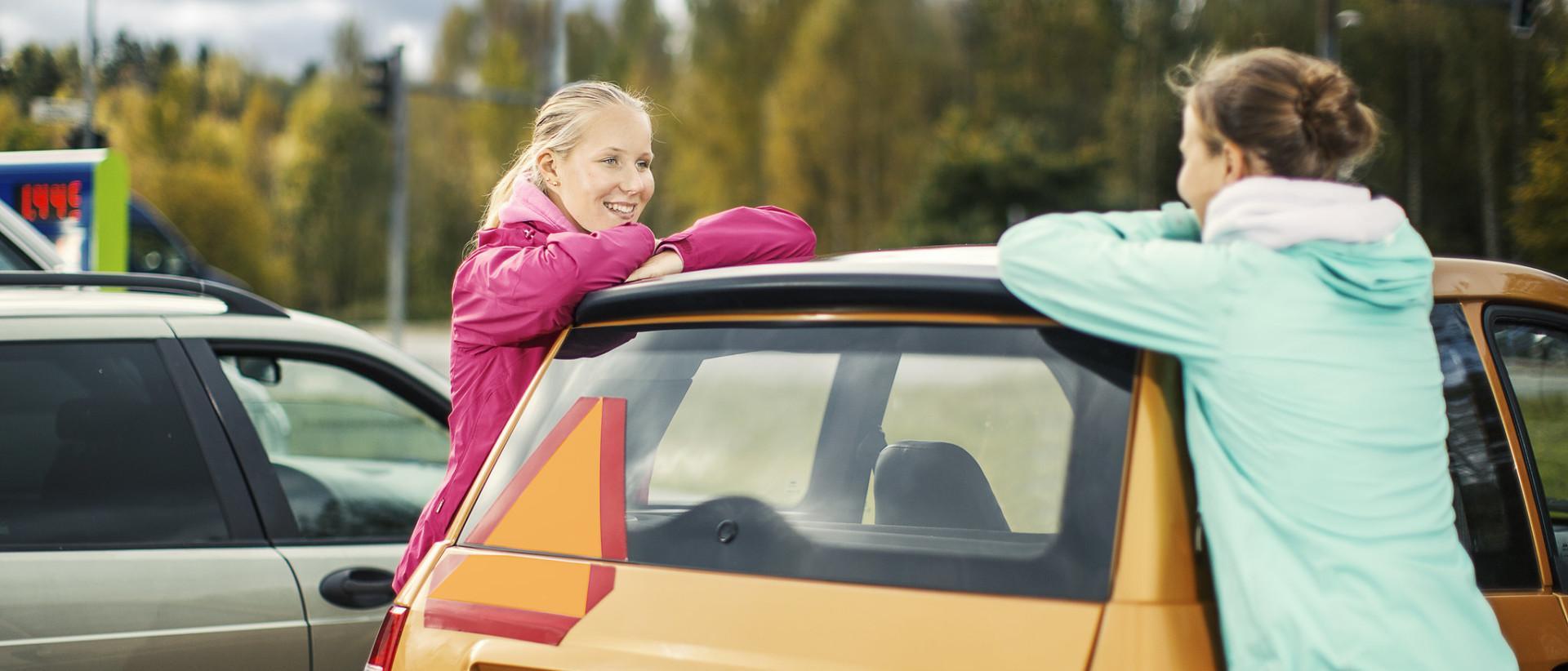 Kuvassa kaksi tyttöä mopoauton vieressä.