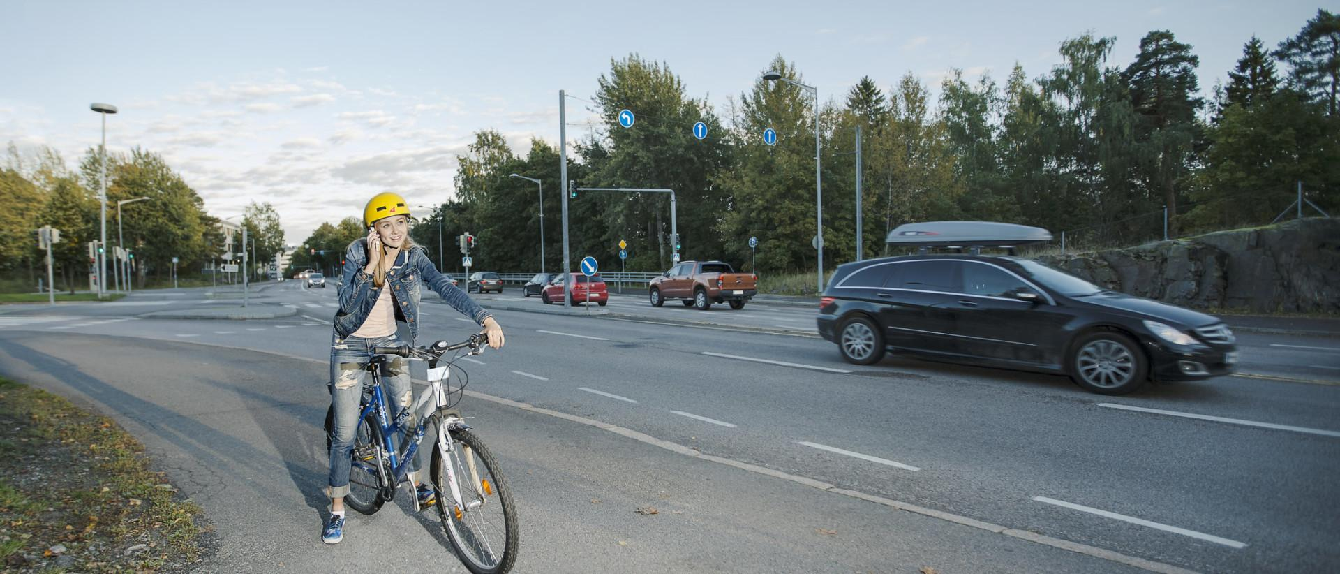 Kuvassa nuori pyöräilijä, joka on pysähtynyt ja puhuu kännykkään.