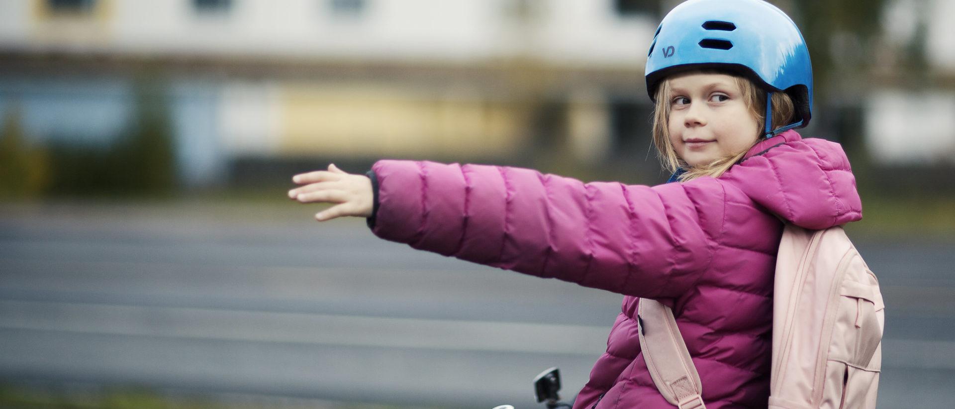 Pyöräilijätyttö näyttää suuntamerkkiä.