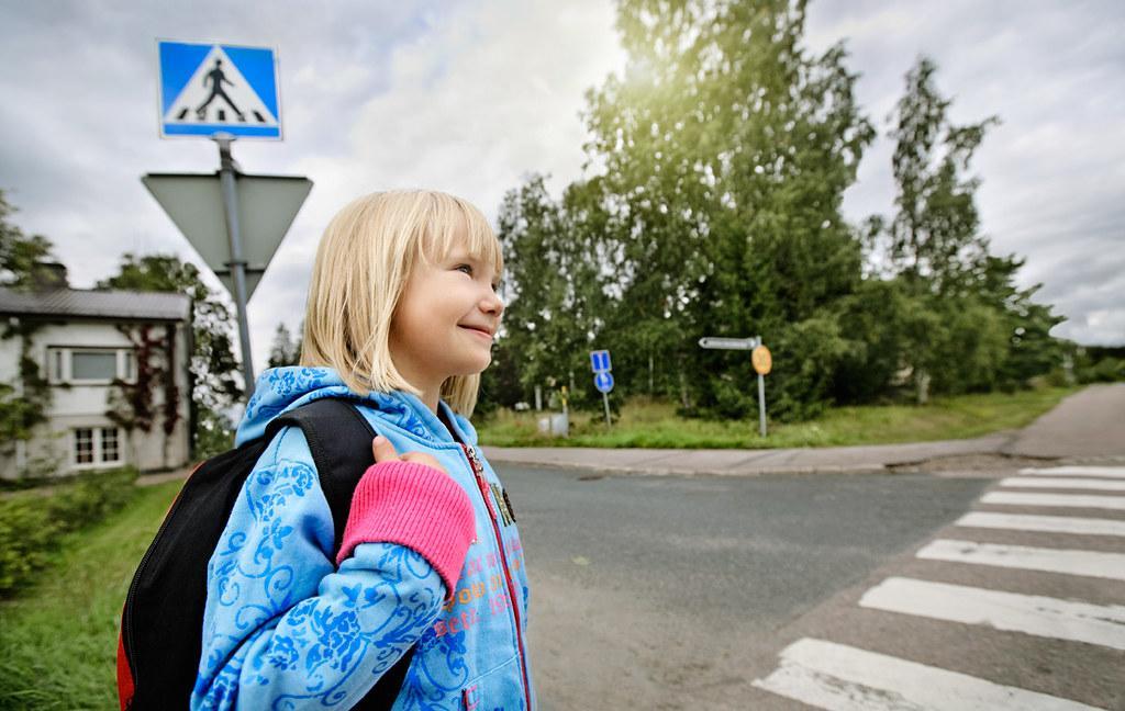 Kuvassa koululainen ylittämässä suojatietä.