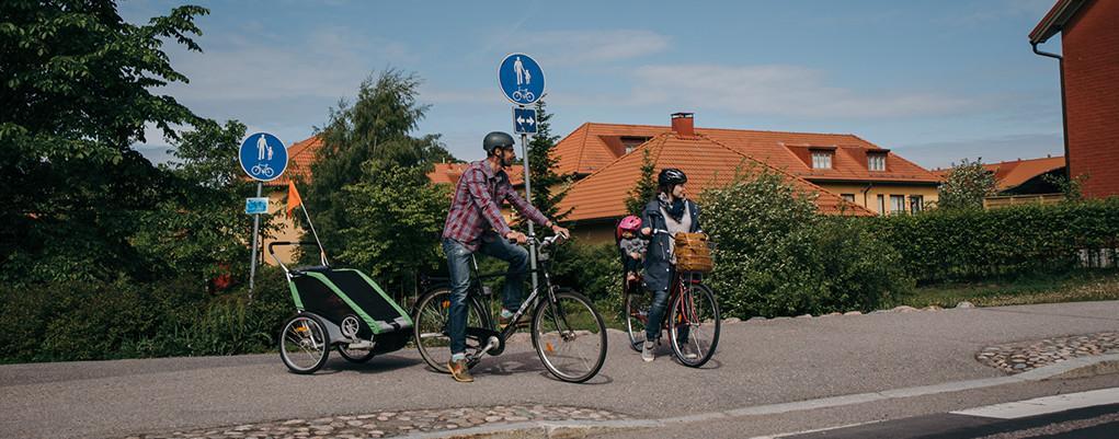 Kuvassa vanhemmat kyyditsevät lapsiaan polkupyörillä.