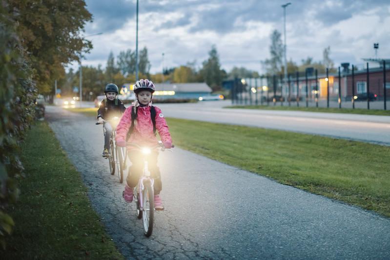 Kaksi kypäräpäistä lasta pyöräilee hämärällä valot loistaen.