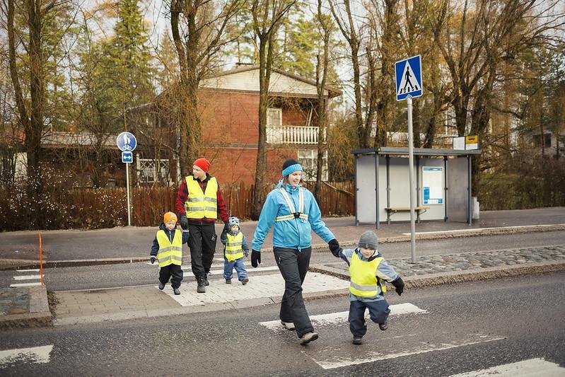 Heijastinliiveihin puetut lapset ylittävät suojatietä aikuisten kanssa.