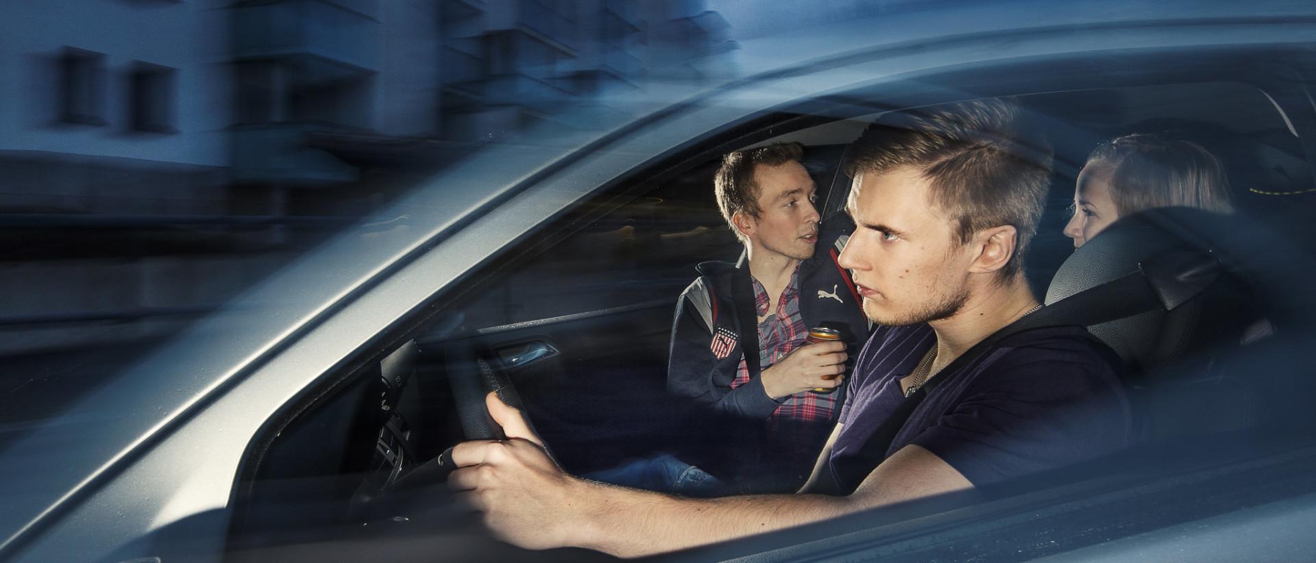 Nuori kuljettaja ajaa henkilöautoa, jonka kyydissä on nuoria matkustajia.