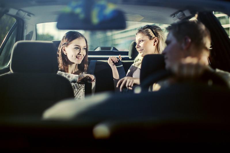 Kuvassa nuort kiinnittävät turvavöitä henkilöauton takapenkillä.