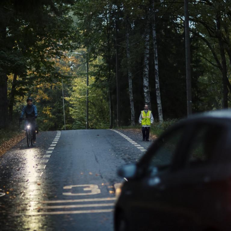 Kuvassa autoilija kohtaa heijastinliivillisen jalankulkijan ja valollisen pyöräilijän hämärällä kylätiellä.