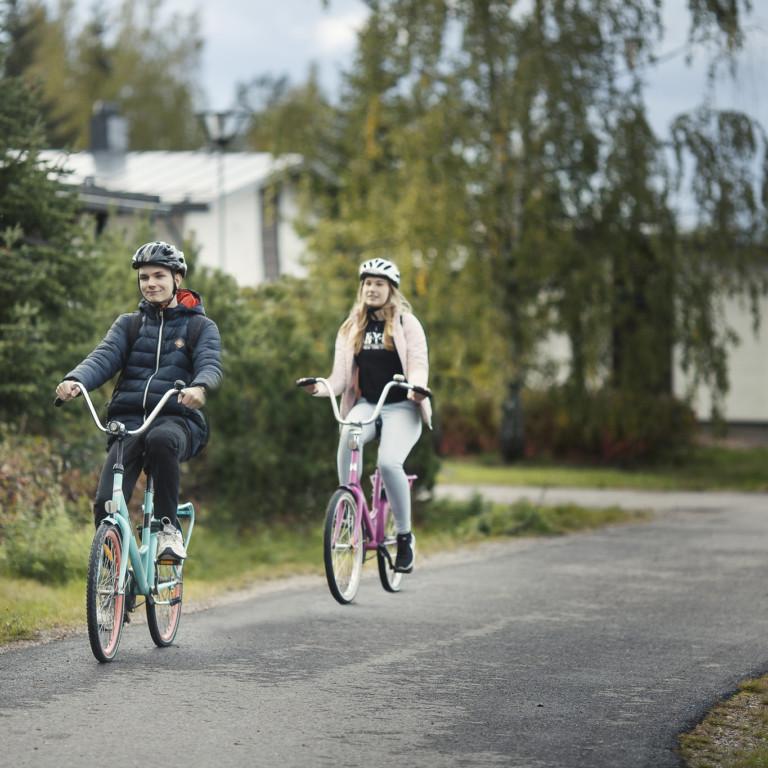 Kaksi nuorta pyöräilee.