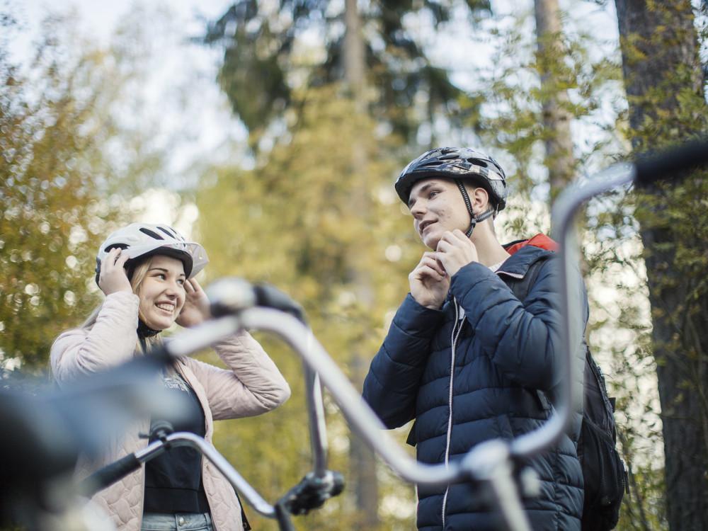Kaksi nuorta pyöräilijää laittaa kypäriä päähän.