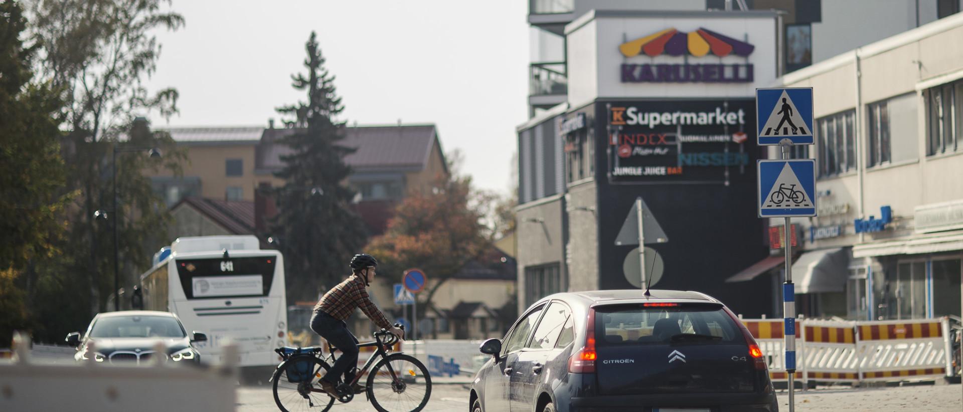 Pyöräilijä ylittää tien, autoilija pysähtynyt suojatien eteen.