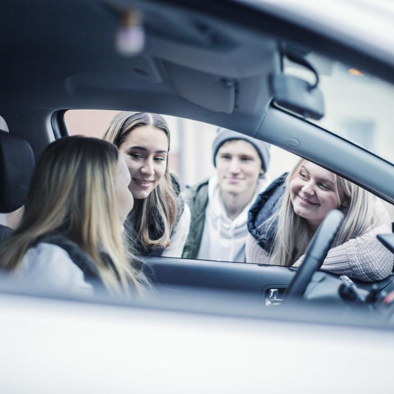 Nuori kuljettaja autossa, jonka ympärillä on muita nuoria.