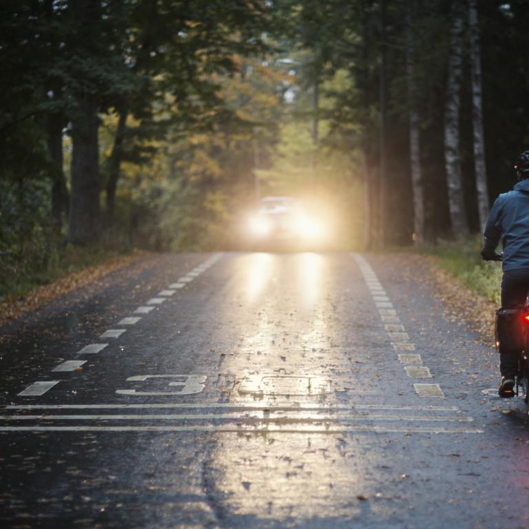 Pyöräilijä pyöräilee pimeässä, takavalo loistaa. Auto tulossa vastaan.