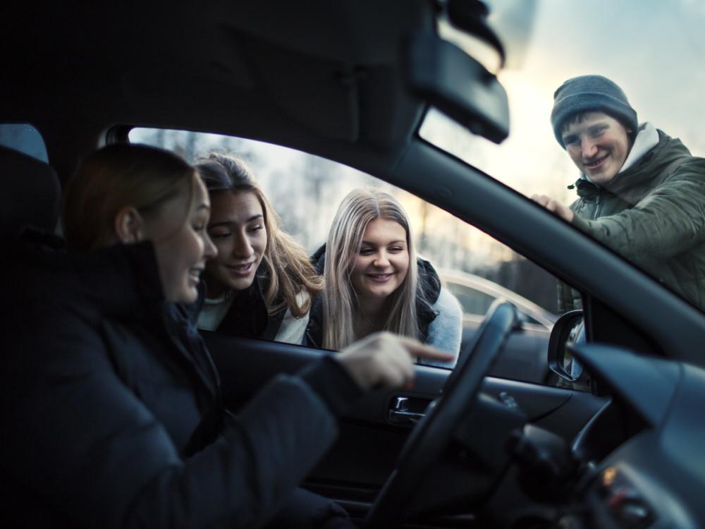 Nuori kuljettaja istuu autossa ja kaverit ovat auton ulkopuolella.