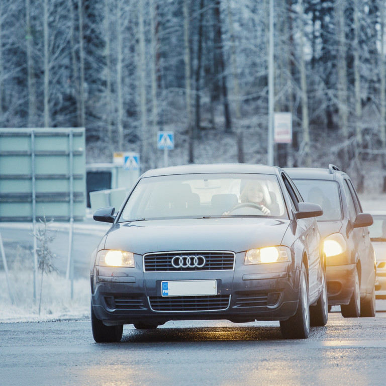 Nainen ajaa autoa, ajovalot palavat. Takana ajaa kaksi autoa.